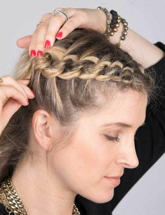Chica poniéndose pasadores en el cabello después de hacer una trenza