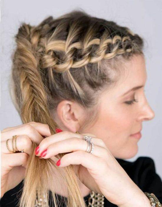 Chica trenzando su cabello en una cola de pez