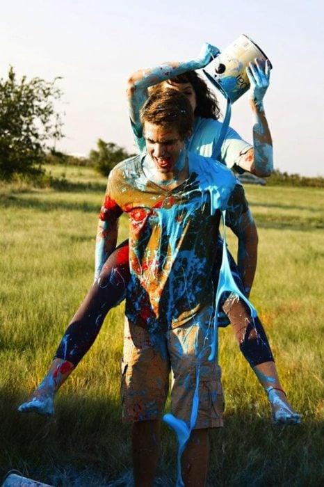 chico cargando chica en la espalda cubiertos con pintura