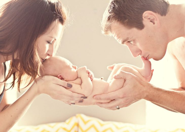 Pareja de novios besando a un bebé mientras lo sostienen