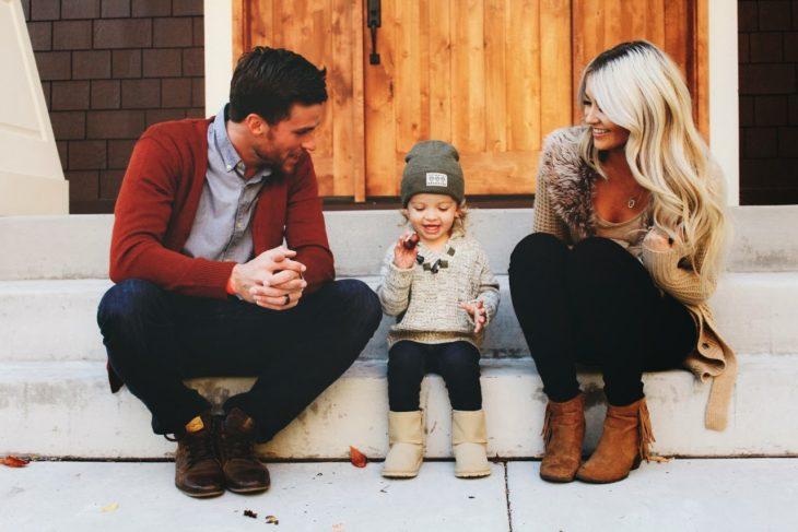Pareja de esposos sentados en las escaleras afuera de una casa conversando con una bebé