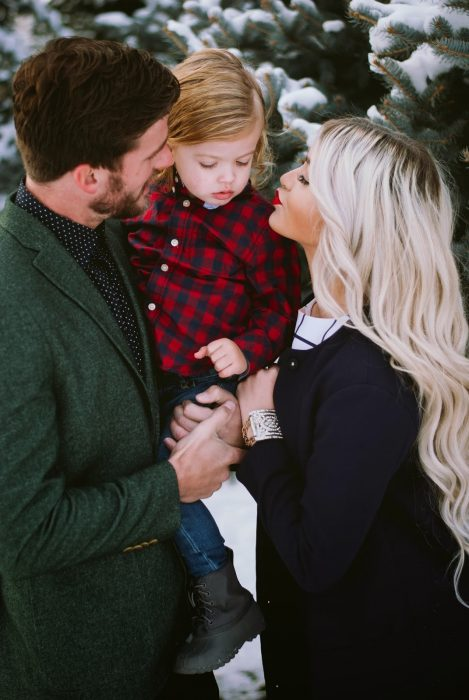 Pareja sosteniendo a un niño en sus brazos mientras le dan un beso