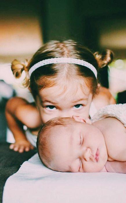 Niña dándole un beso en la mejilla a un bebé que está recostado en la cama