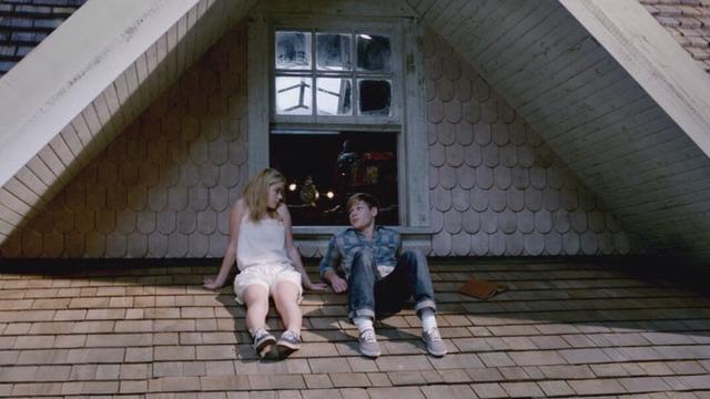 Chico y chica sentados en el tejado de una casa hablando