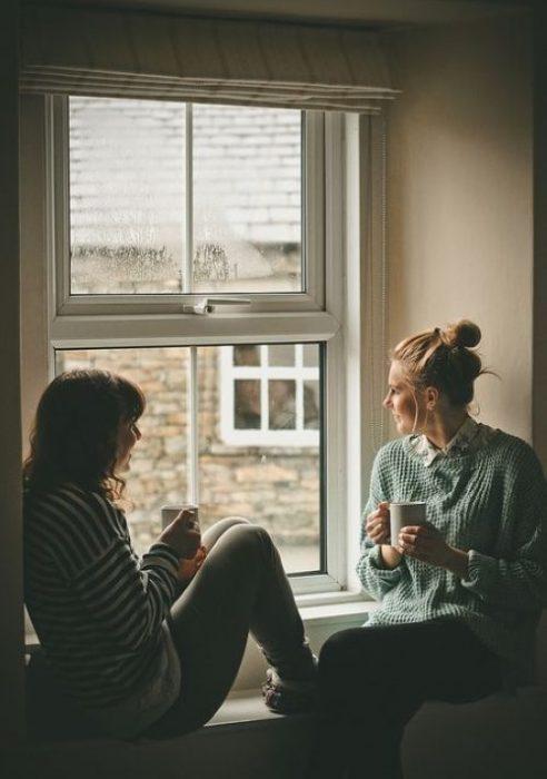 Amigas sentadas frente a una ventana conversando y bebiendo café