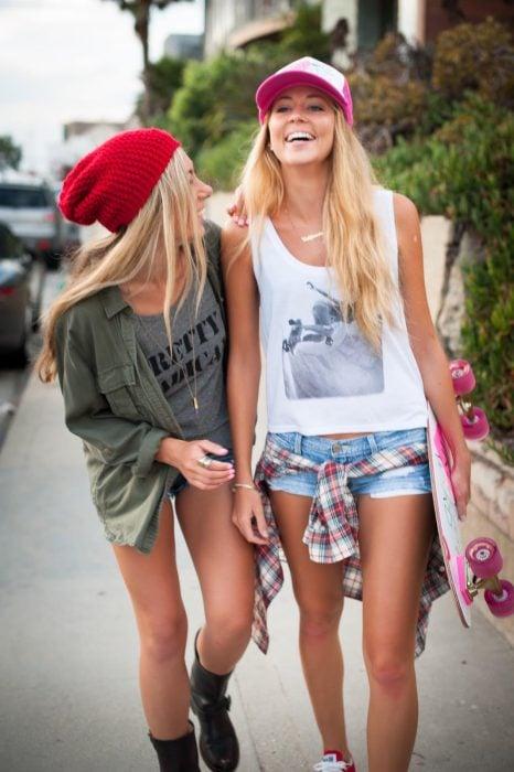 Chicas caminando por la calle mientras una de elas usa una patineta