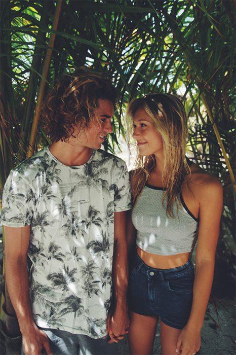 Pareja de novios parados bajo una palmera mientras se están viendo de frente