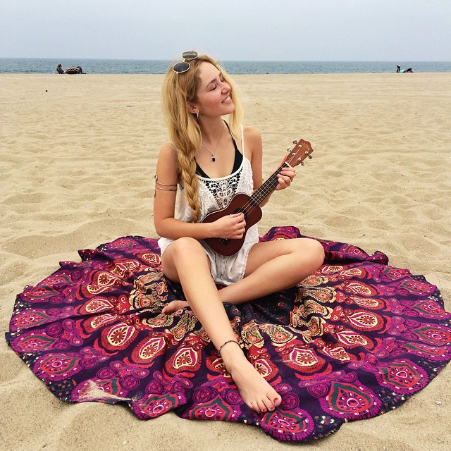 Chica sentada en la playa sobre un tapete mientras toca una guitarra