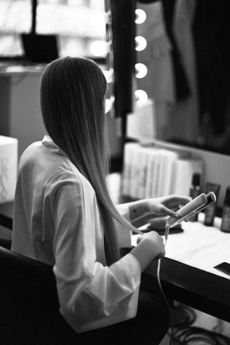 Chica frente a un espejo cortándose el cabello