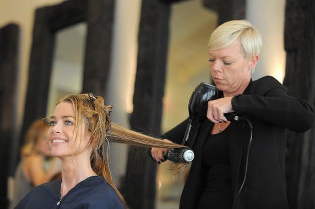 Chica con el estilista sentada mientras le secan el cabello