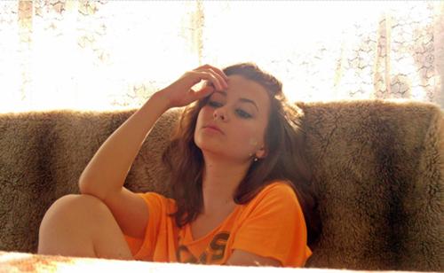 Chica de camisa naranja sentada en un sofá y tocándose la cabeza