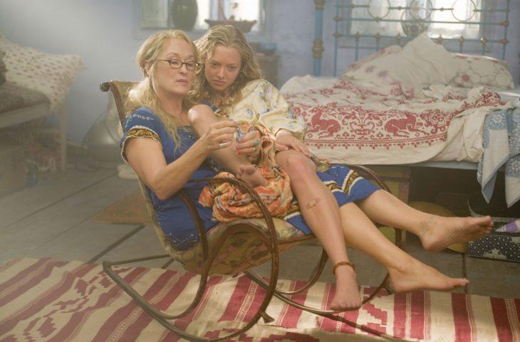 Escena de la película mama mia, chica sentada en el regazo de su madre mientras está le pinta las uñas
