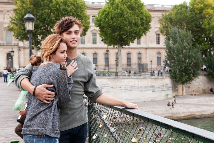 Escena de la película LOL con miley cyrus chicos abrazados en el puente mientras miran la ciudad