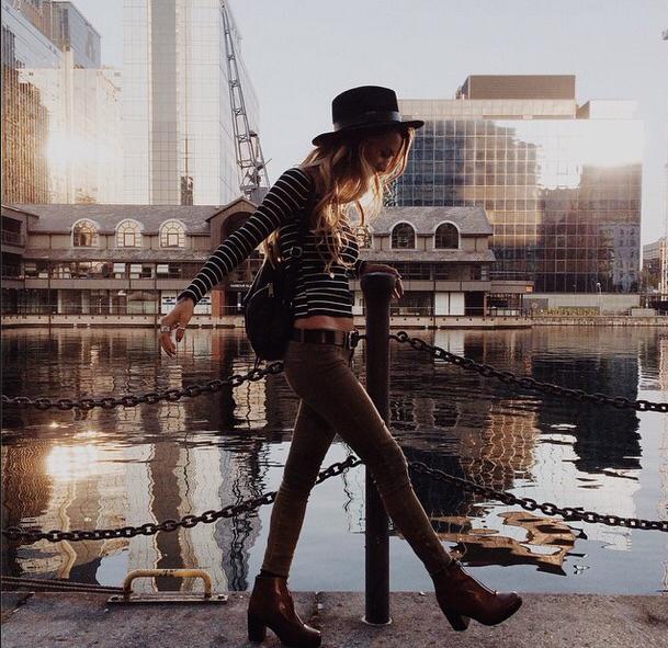 Chica caminando por la calle mientras observa el mar