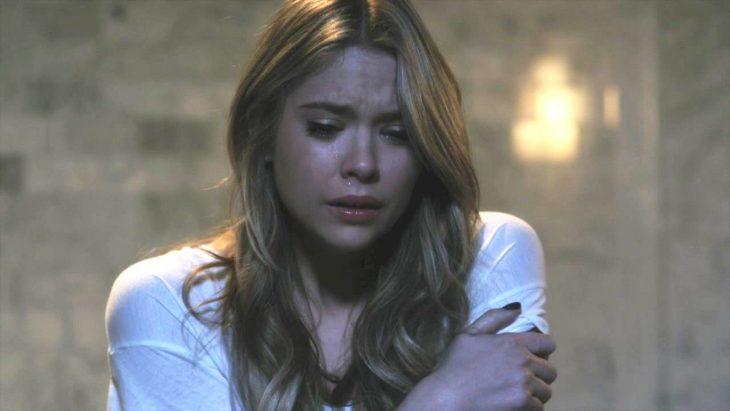 Hanna de la serie pretty little liars llorando mientras está frente a la ventana de su cuarto