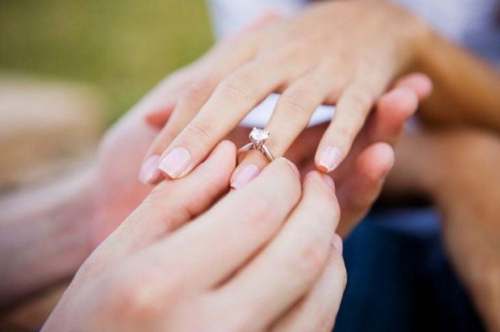 Pareja colocando el anillo de compromiso