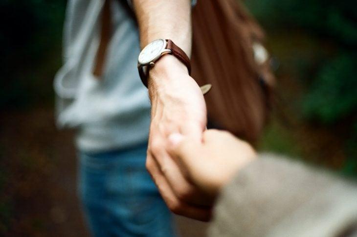 Chico con un reloj tomando de la mano a su novia
