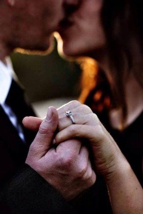 Pareja mostrando el anillo de compromiso y besándose