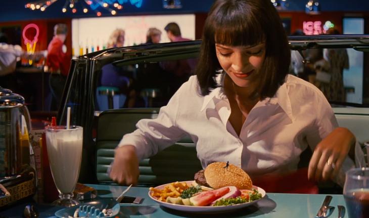 Escena de la película pulp fiction chica sentada comiendo hamburguesa