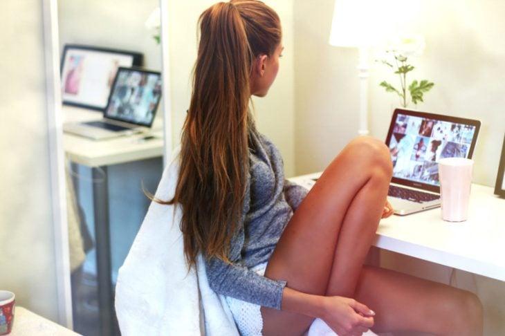 Chica sentada frente a una computadora viendo ropa en internet