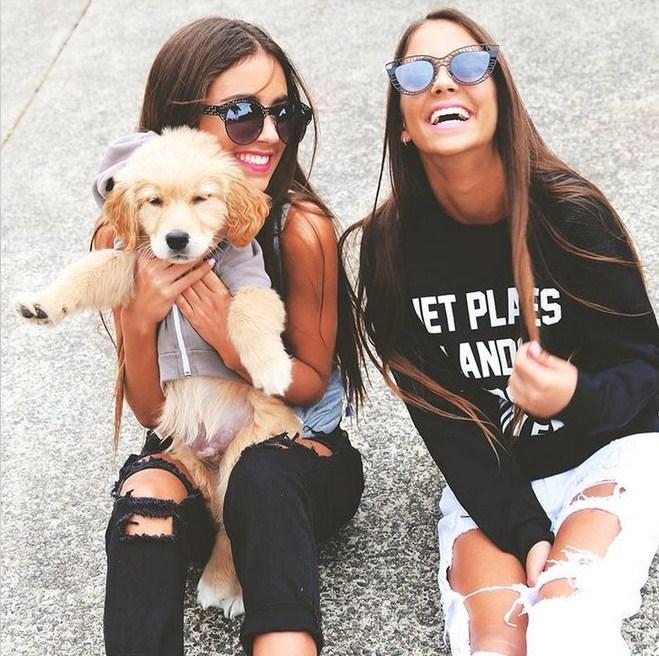 Amigas en ca calle riendo sosteniendo a un perrito