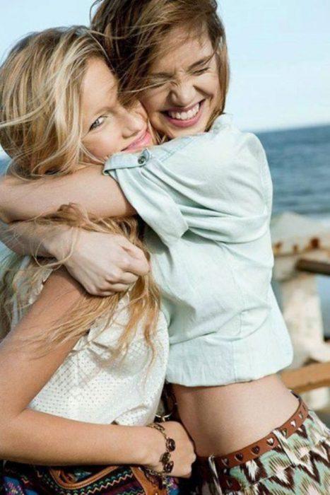 Amigas abrazandse fuertemente y sonriendo