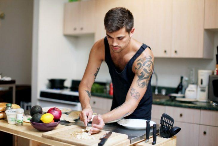 Chico cocinando en una cocina mientras pica verduras sobre una tabla