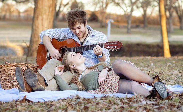 Chico con una guitarra mientras esta recostado en el pasto con una chica