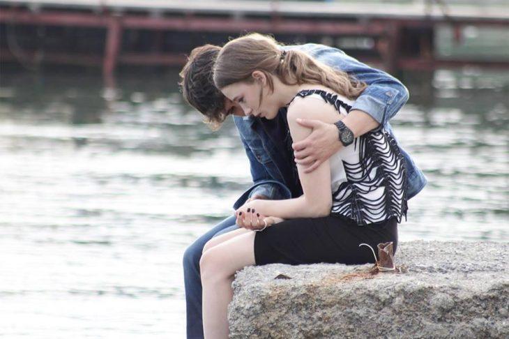 Chico abrazando a una chica mientras están sentados en una piedra