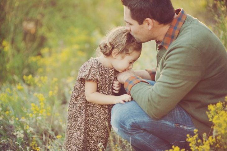 papá besando a su pequeña hija en la frente