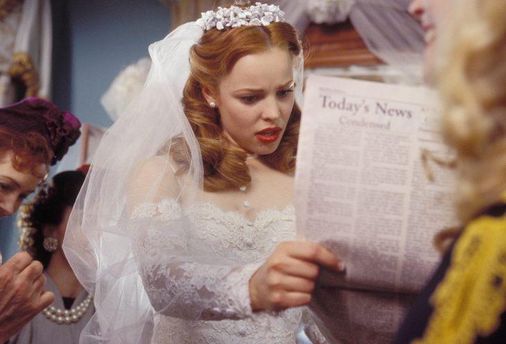 Escena de la película el diario de noah, allie leyendo un periódico mientras tiene un vestido de novia puesto