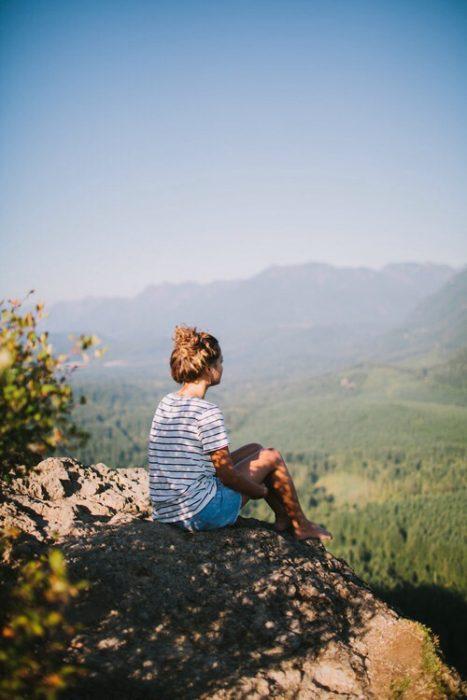Chica sentada en una roca mirando al horizonte