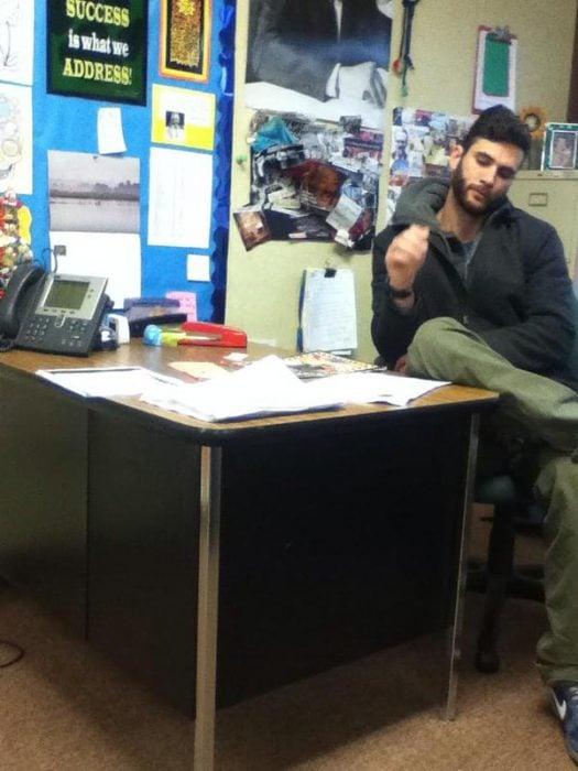 Maestro atractivo sentado en su escritorio