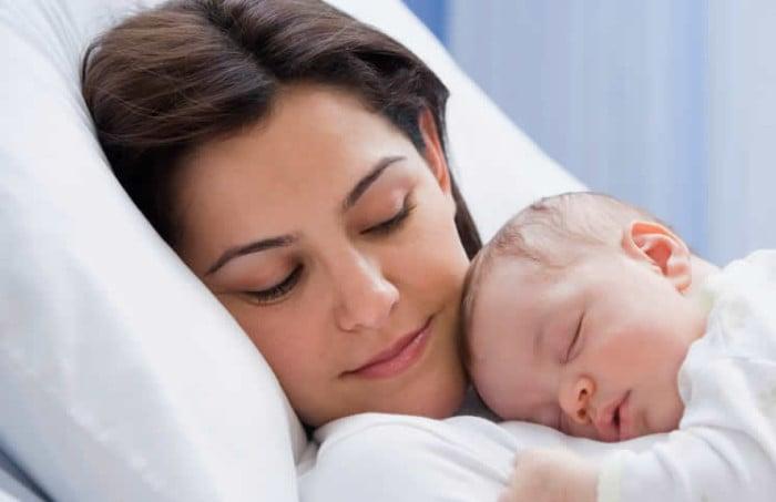 Mamá que descansa junto a su bebé