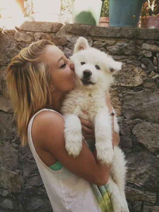 Chica abrazando a un perro Samoyedo