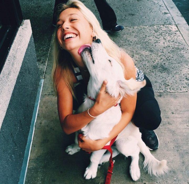 Chica abrazando a un perro en la calle