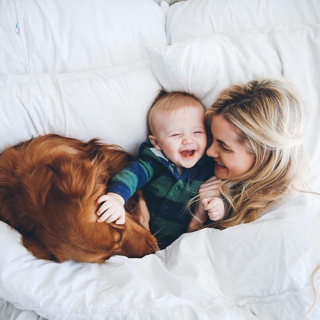 Perro, bebé y chica en una cama acostados