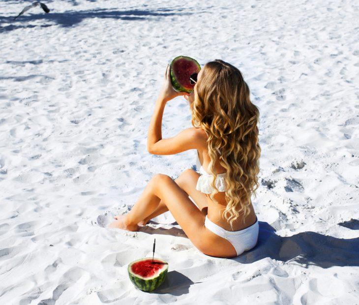 Chica comiendo sandía en la playa