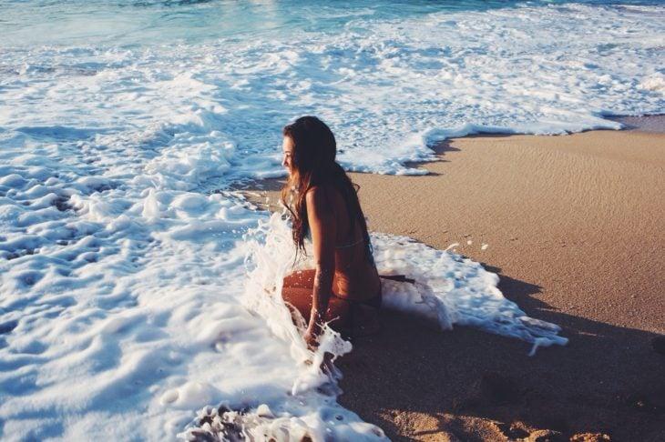 Chica disfrutando de las olas del mar