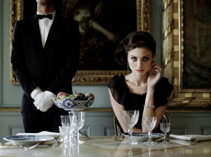 Mujer con mirada penetrante sentada en la mesa