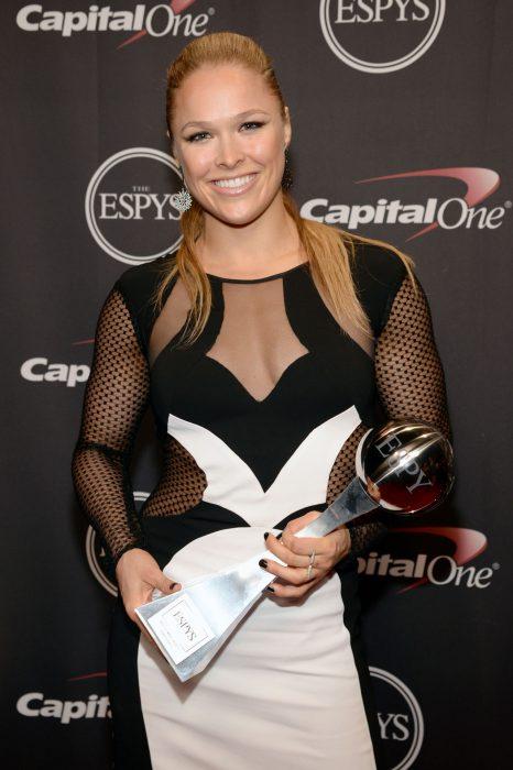 luchadora de la UFC Ronda Rousey sosteniendo un premio en sus manos