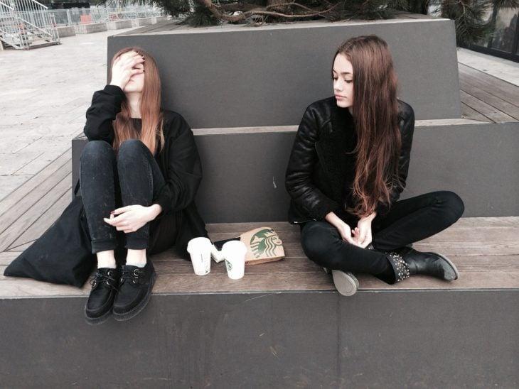 Chicas sentadas en una banca con café de Starbucks