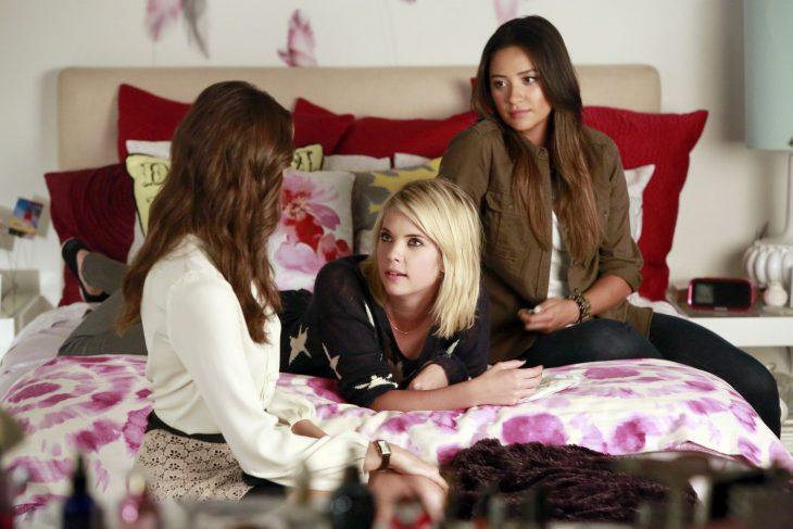 Escena de la serie PRETTY LITTLE LIARS chicas sentadas en la cama conversando