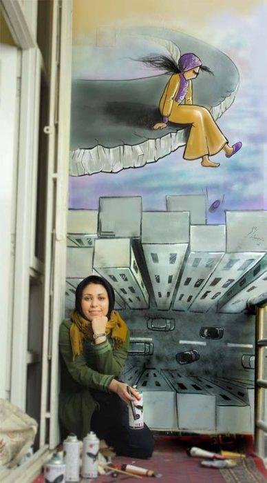 Artista callejera parada junto a su mural mientras sostiene una lata de aerosol en sus manos