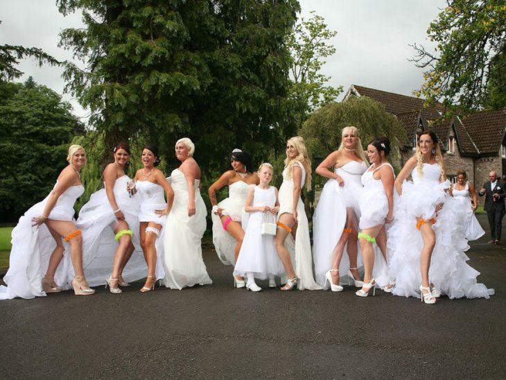 Damas de honor de pareja gay enseñando la liga