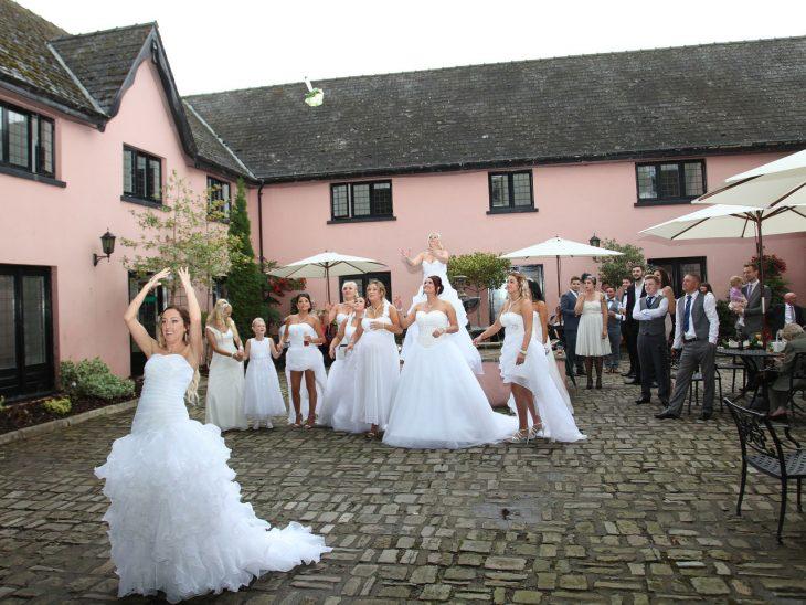 Damas de honor vestidas de novia lanzando el ramo