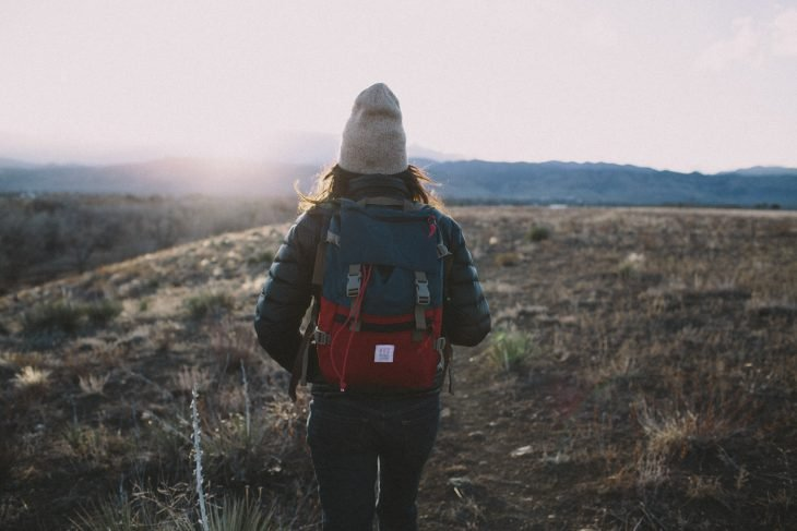 Chica con una mochila observando el paisaje