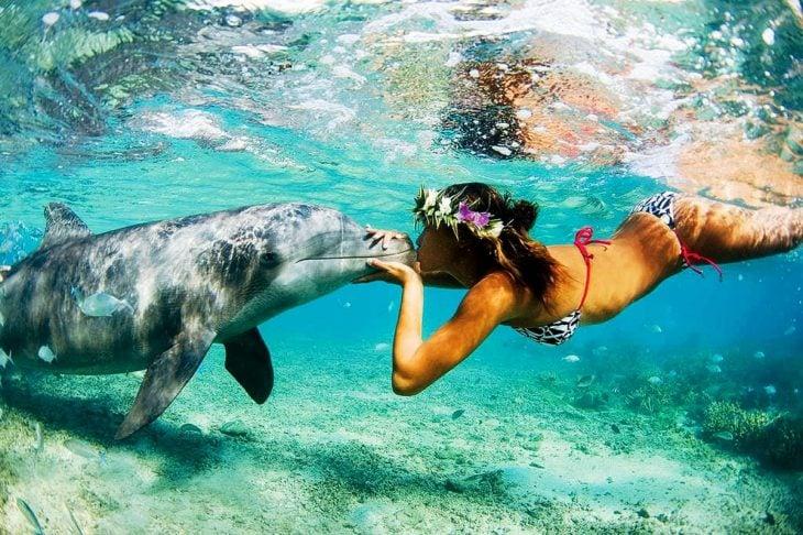 Chica besando un delfín