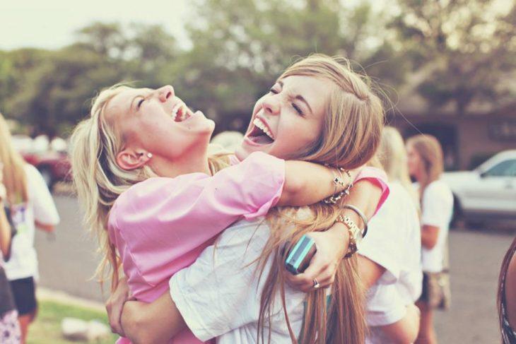 Amigas abrazadas y sonriendo