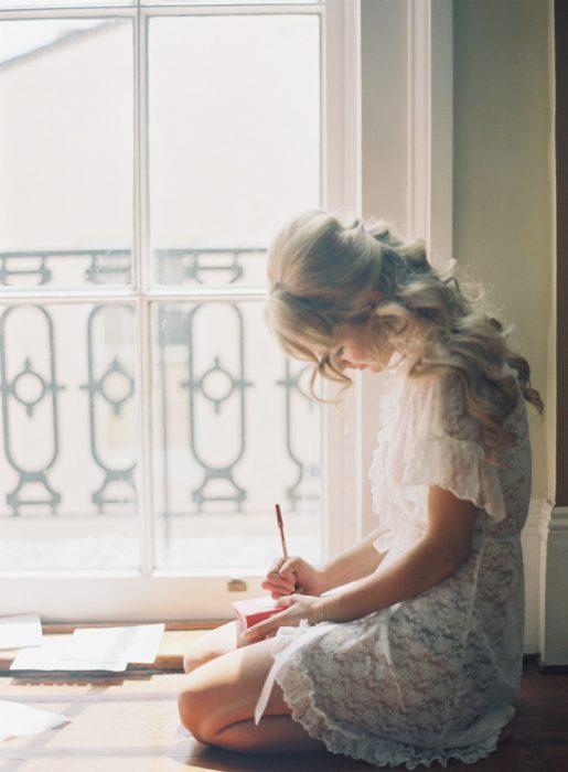 Chica sentada en el suelo escribiendo